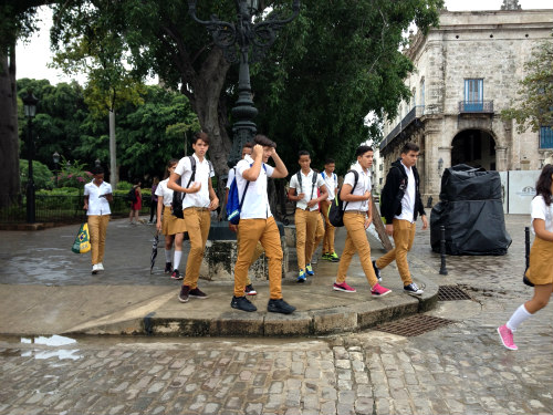 Teens on a school field trip. Uniforms yield to individuality by way of socks, shoes and back packs.
