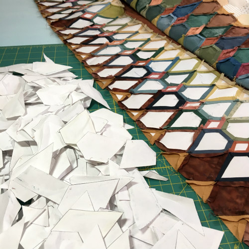 Once the quilt top is completely assembled, at last, all of the paper pieces can be removed! Aa a mountain of paper pieces grows, one can see the wisdom in reusing papers.