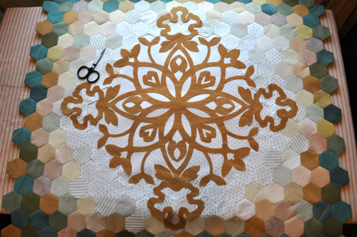 Fusing the center medallion onto the quilt top. Tiny, sharp scissors trim any stray threads before fusing.