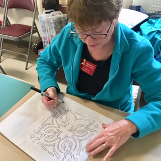 Pam Mueller tracing one of her unique designs.