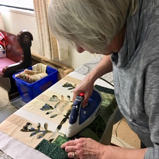 Sue Hopkins fusing Tulips to one end of her table runner.