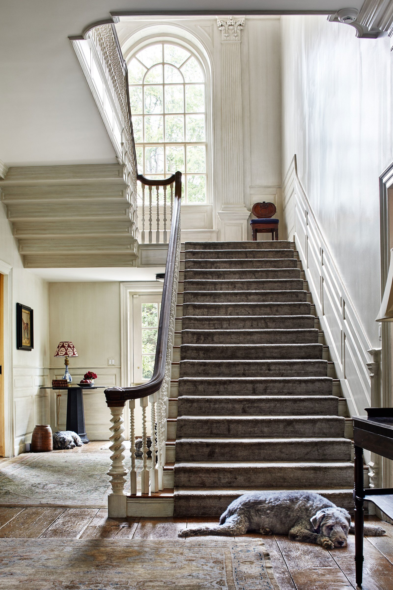 The home's foyer features an exceptionally spacious staircase, with a runner rug sourced from David Zadeh.