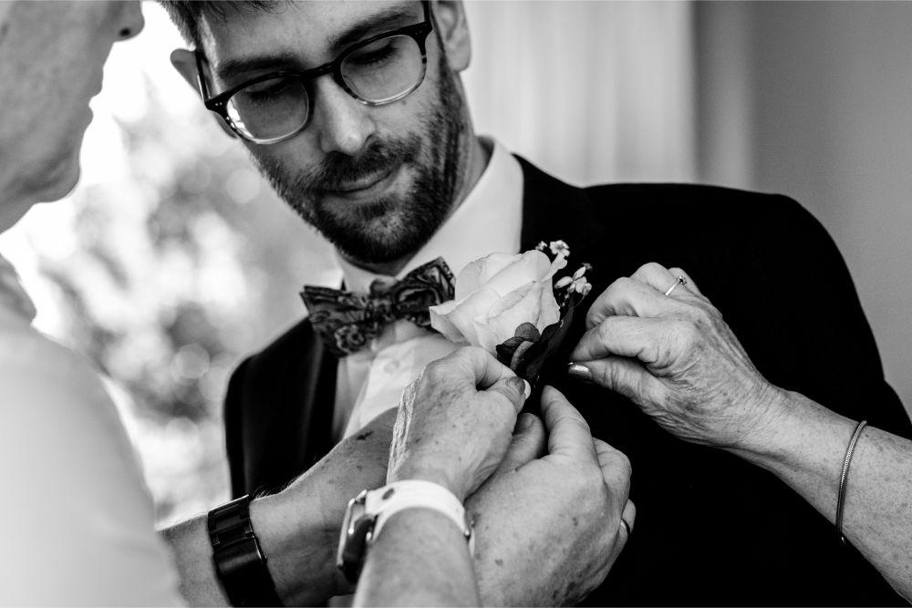 Corsage vastmaken bij bruidegom