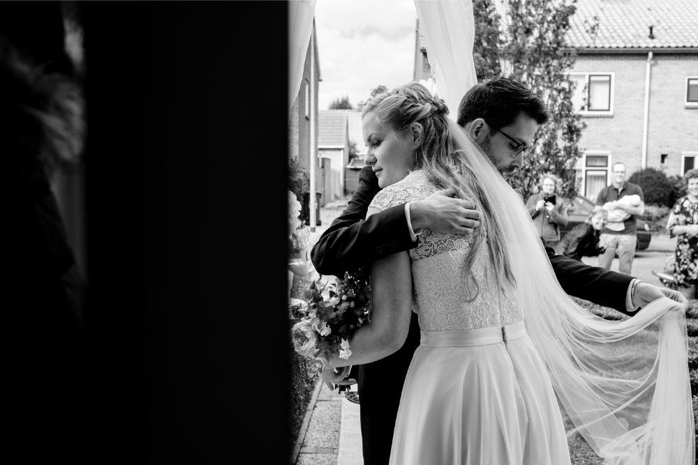 Bruidegom bewondert de jurk van de bruid