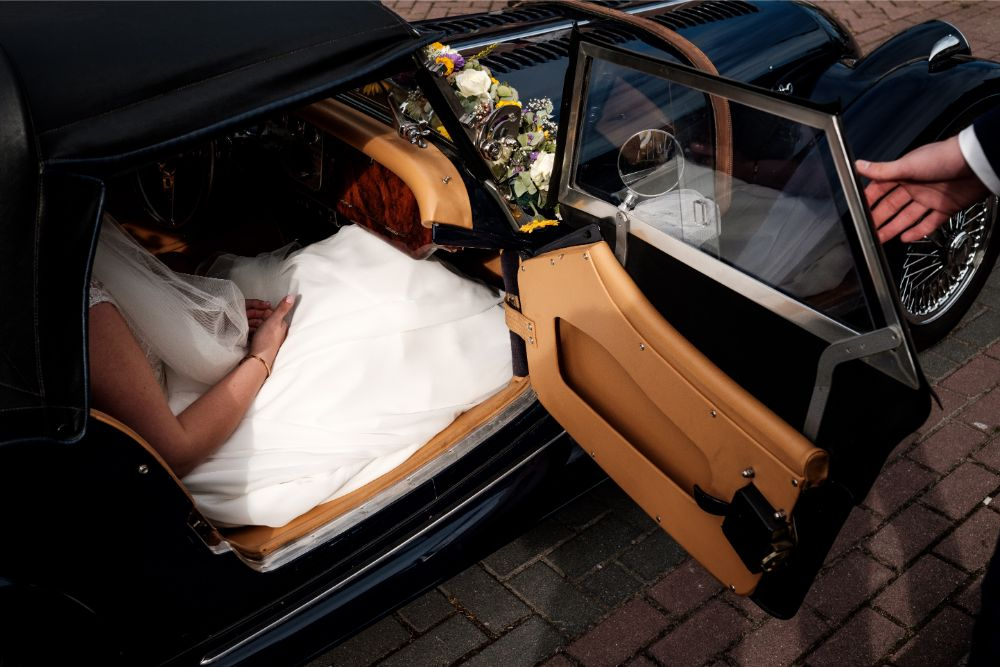 Bruidegom helpt bruid in bruidsauto