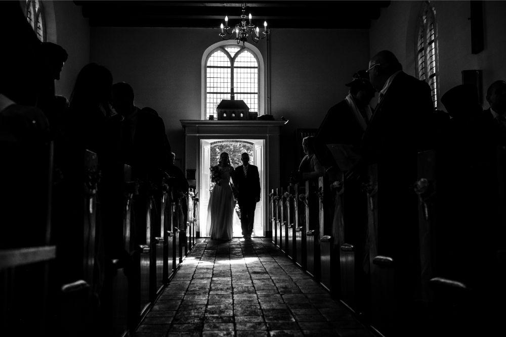Bruid en haar vader lopen de kerk in