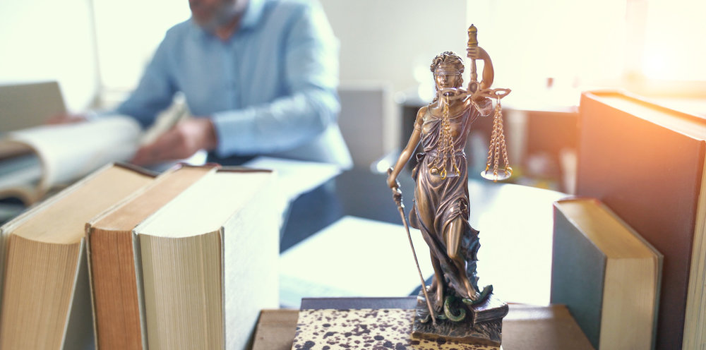 lawyer working at desk - Charged With Driving While Suspended/Revoked in California  The Law Offices of Bryan R. Kazarian - Los Angeles County Criminal Defense Attorneys - property, juvenile, petty theft, DUI, misdemeanor, and felony Criminal Law