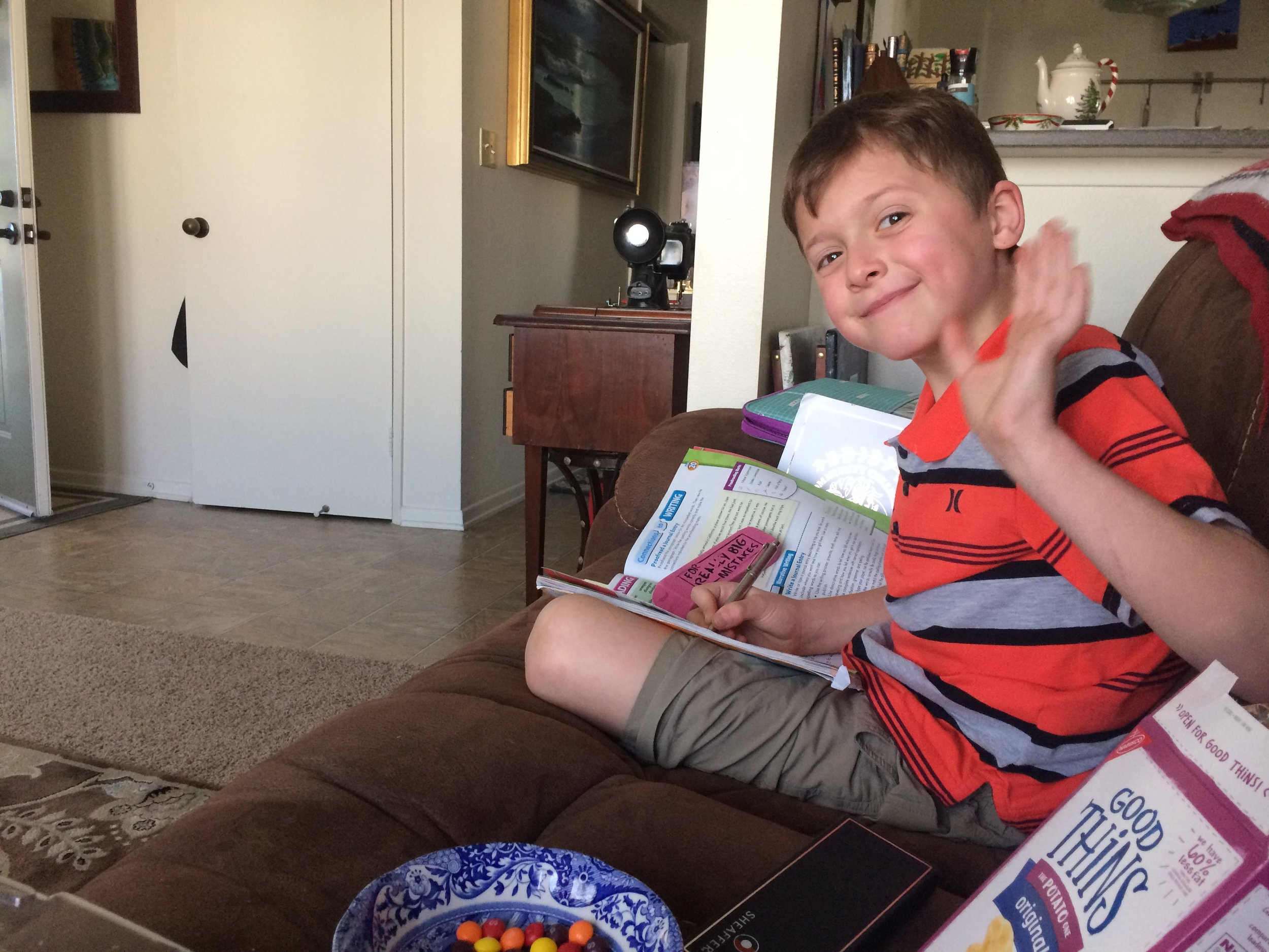 """My boy doing his homework today, while eating Skittles. He can't help eating junk food. His mother ate all the """"Good Thins,"""" leaving him with no choice but to eat the crap. Bad mommy."""