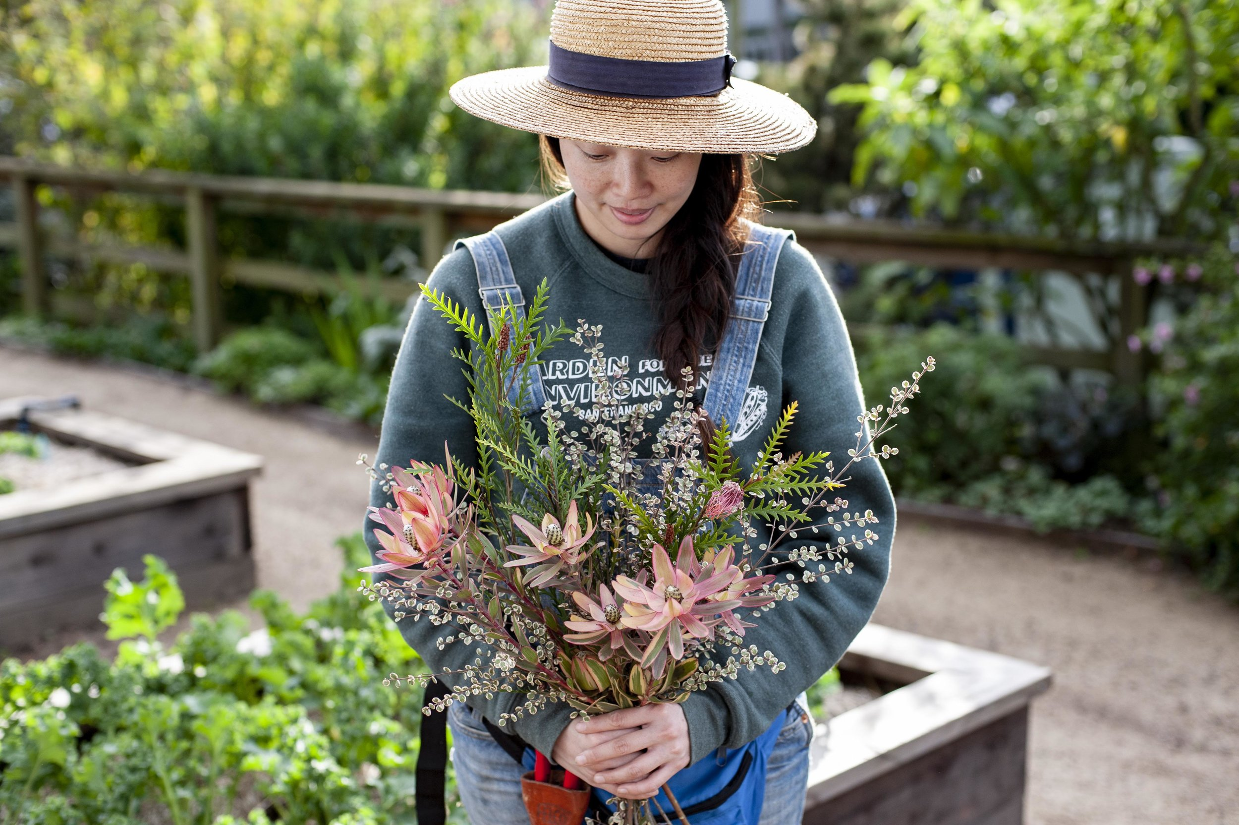 Volunteer extraordinaire Hana posing with a winter bouquet of  Leucadendron ,  Grevillea , and  Lophomyrtus .