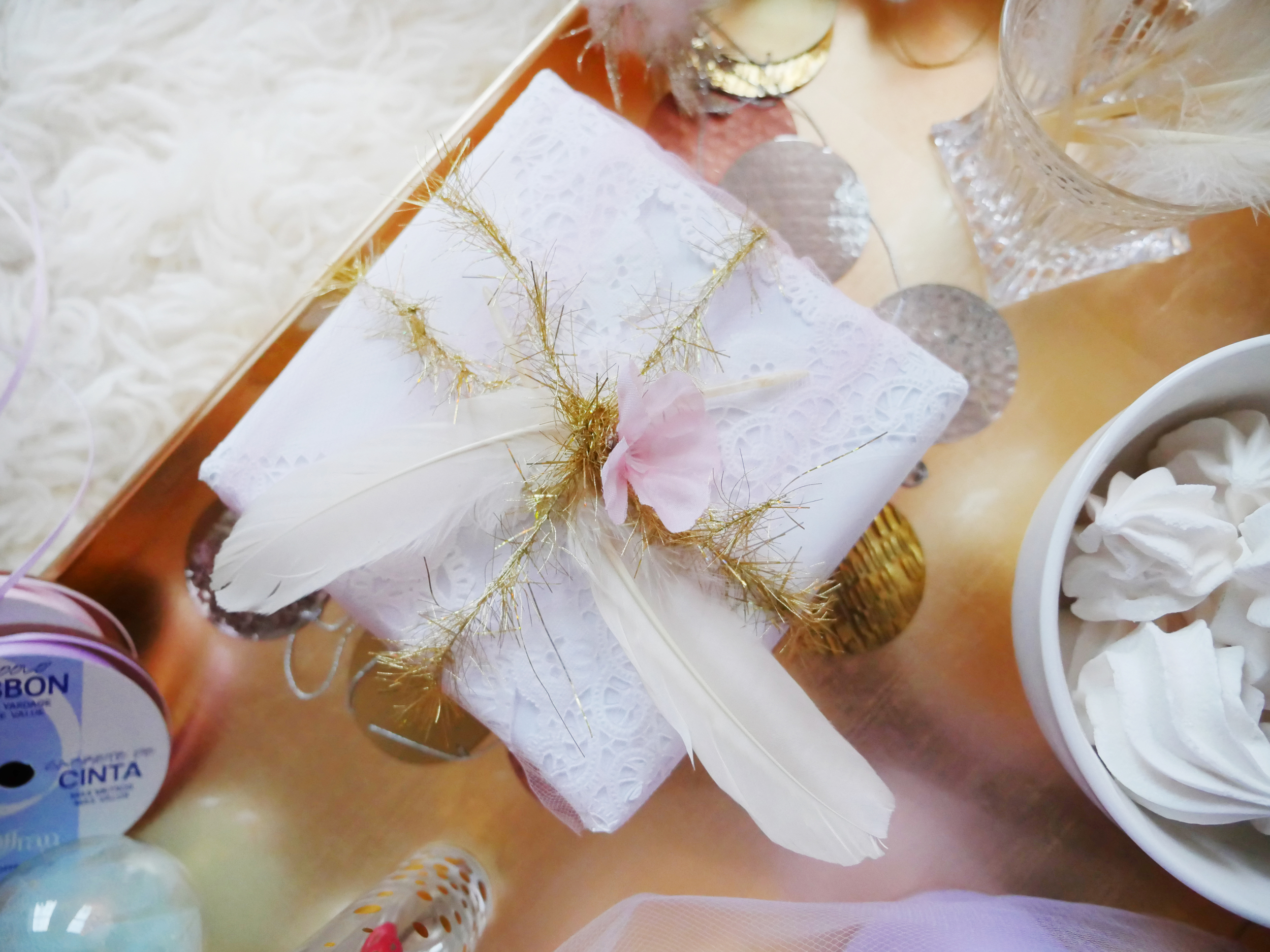 To go the Extra Mile: We wrapped the gift with doilies. Yes!!! Then we wrapped a pink Tulle over it for a soft pinkish hue, tying gold festive trimming with feathers and a cute artificial flower!