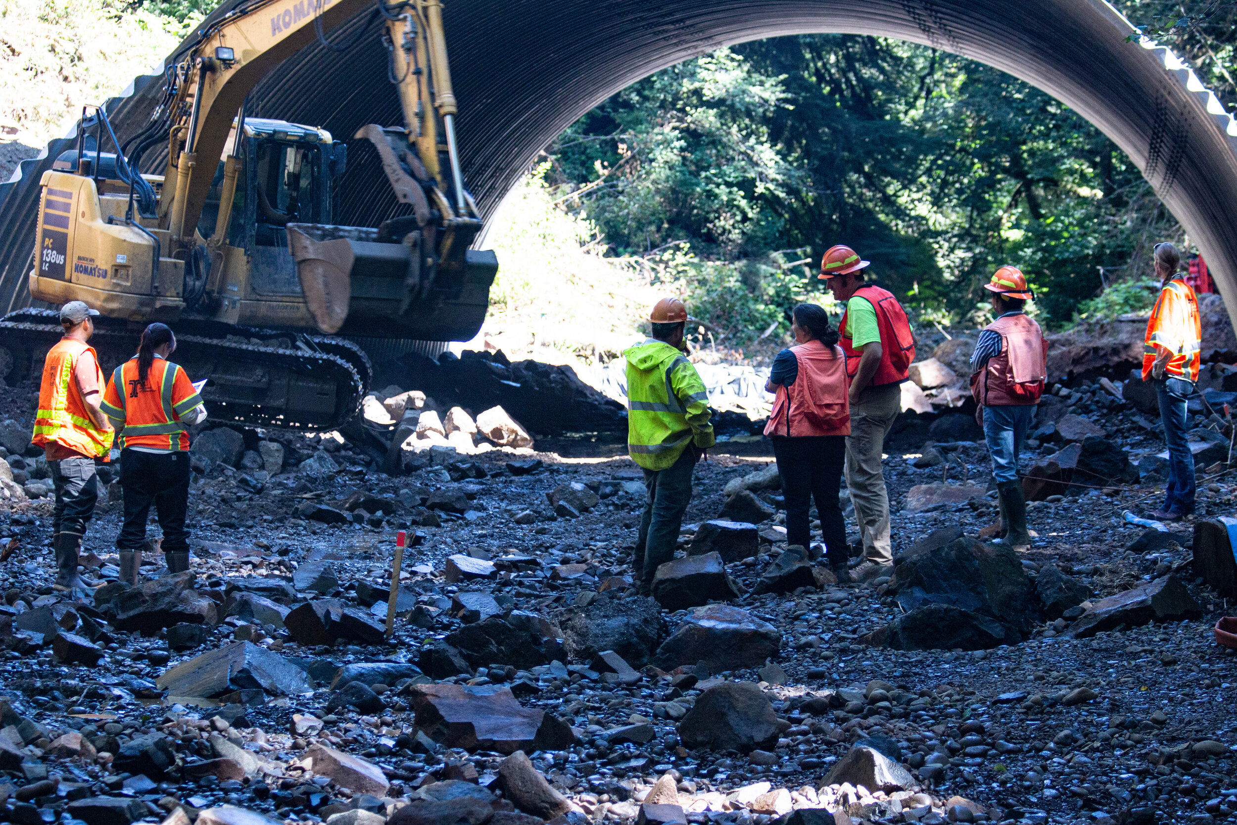 ODOT, MCWC, and USFS personnel view the placement of stream simulation under the new culvert to ensure they meet the engineered designs, meant to mimic a natural streambed.