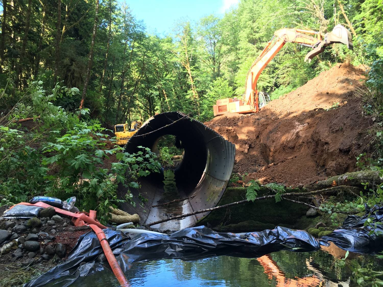 Removal of a large amount of fill from the road surface above the old culvert was required prior to its removal.