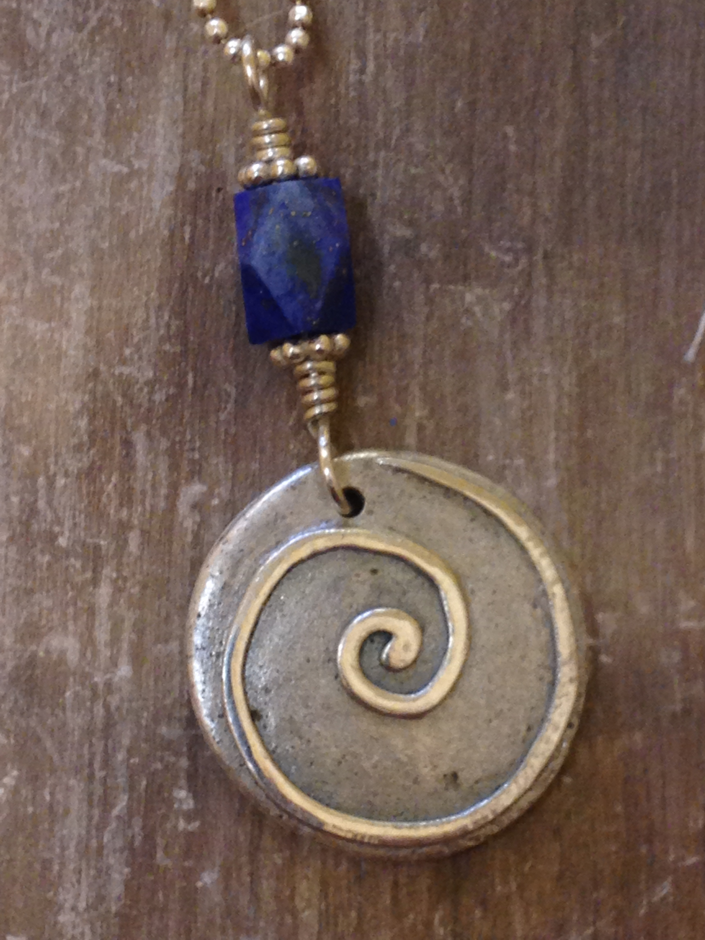 The original Circle of Life pendant with spiral and lapis lazuli bead. Note the organic texture the ash creates in the silver.