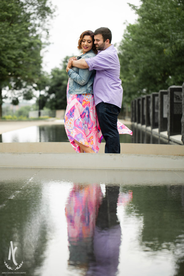 An engaged couple in Nashville, TN, with their reflection in the water