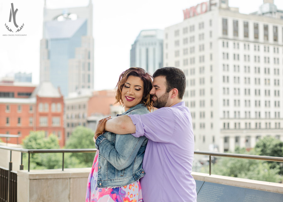 An engaged couple in front of the Nashville, Tennessee skyline
