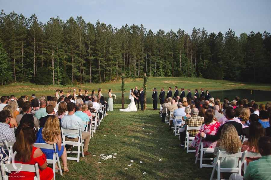 Outdoor Summer ceremony in front of pond and trees