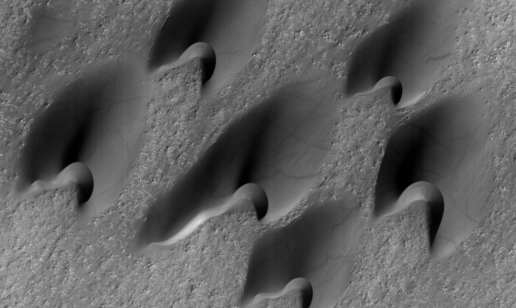 """Barchan dunes on Mars. This pattern shows wind direction by the """"horns"""" on the side of the dune. The weird faint scar marks on these dunes are from dust devils! Image from HiRISE/ASU."""