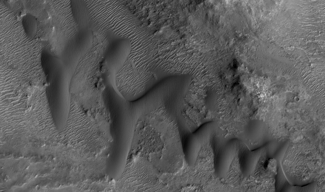 Star dunes on Mars. Notice the different shape than barchan dunes. These shark-tooth looking dunes have more chaotic wind pattern areas. Image from HiRISE/ASU.