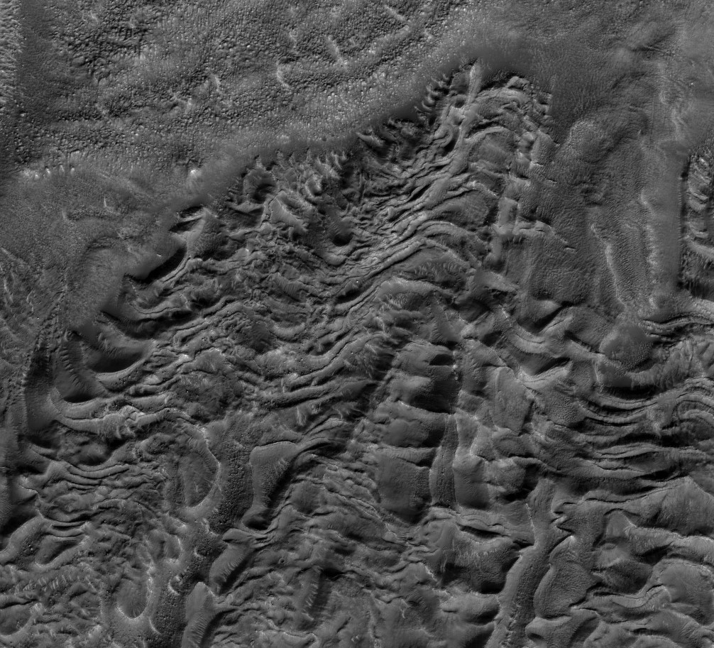 HiRISE image of wavy terrain disrupted by a past moving glacier.