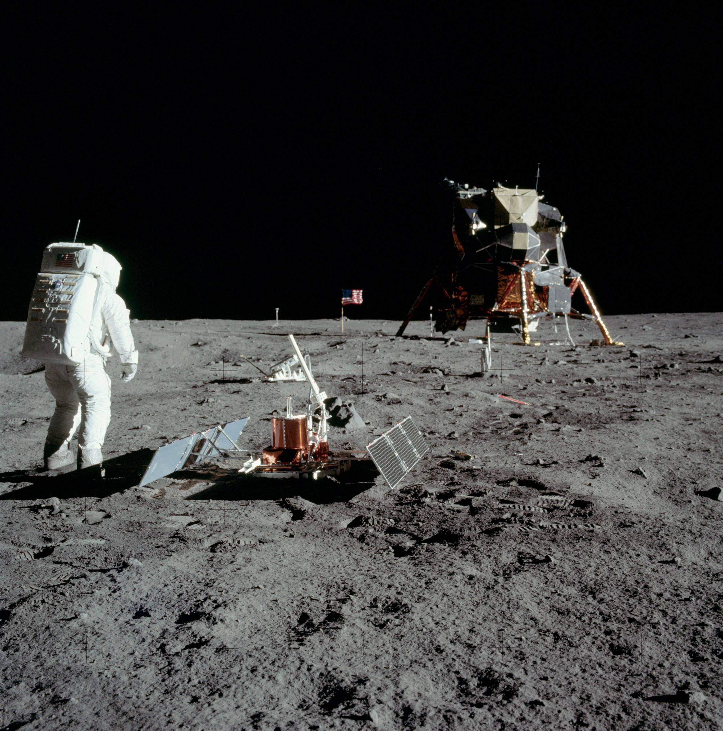Apollo 11 astronaut Buzz Aldrin with the seismic experiment. Solar panels have deployed on the left and right and the antenna is pointed at Earth. Image credit: NASA