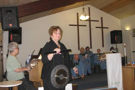 The Rev. Dianne O'Connell rings gong and Elder Smoke rings bells for a total of 350 chimes to signify the goal of cleaning up our air so that it does not exceed 350 parts per million of carbon dioxide.