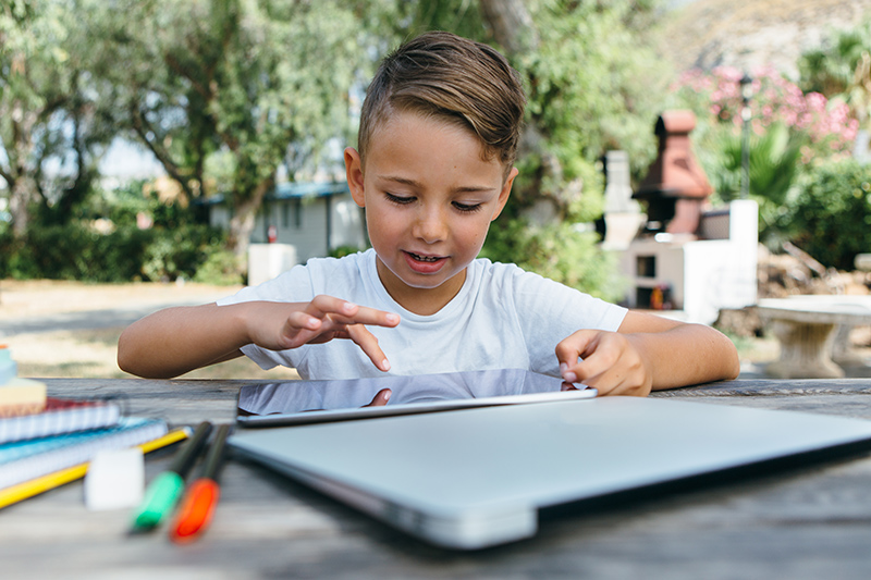 kid-with-tablet-studying-in-garden.jpg