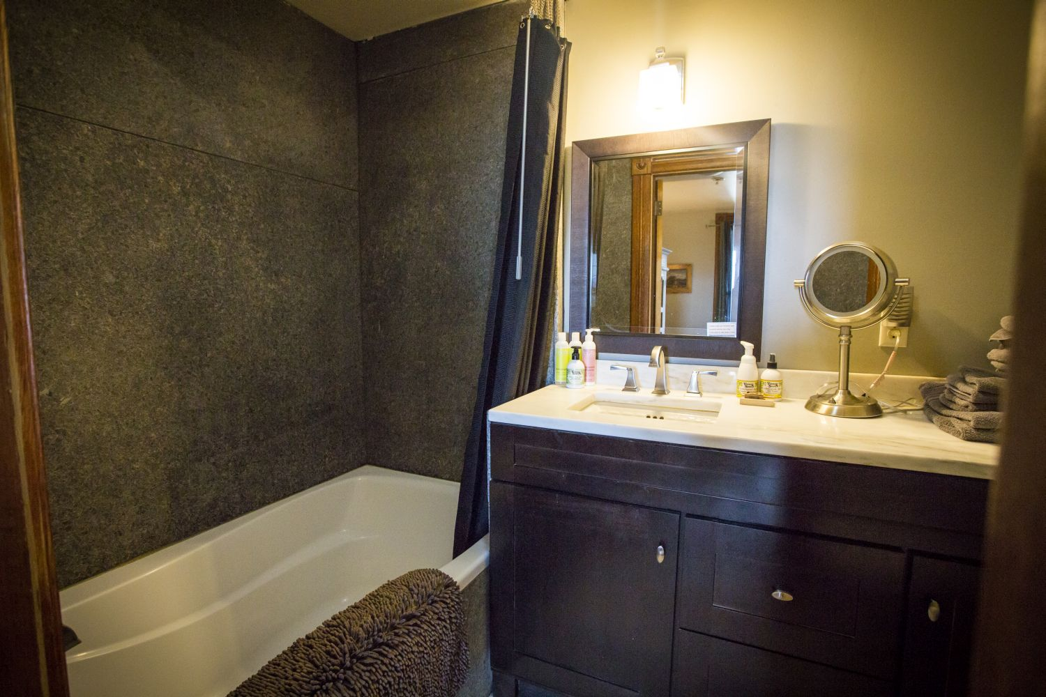 The master bathroom has an oversize tub, marble counter and floor