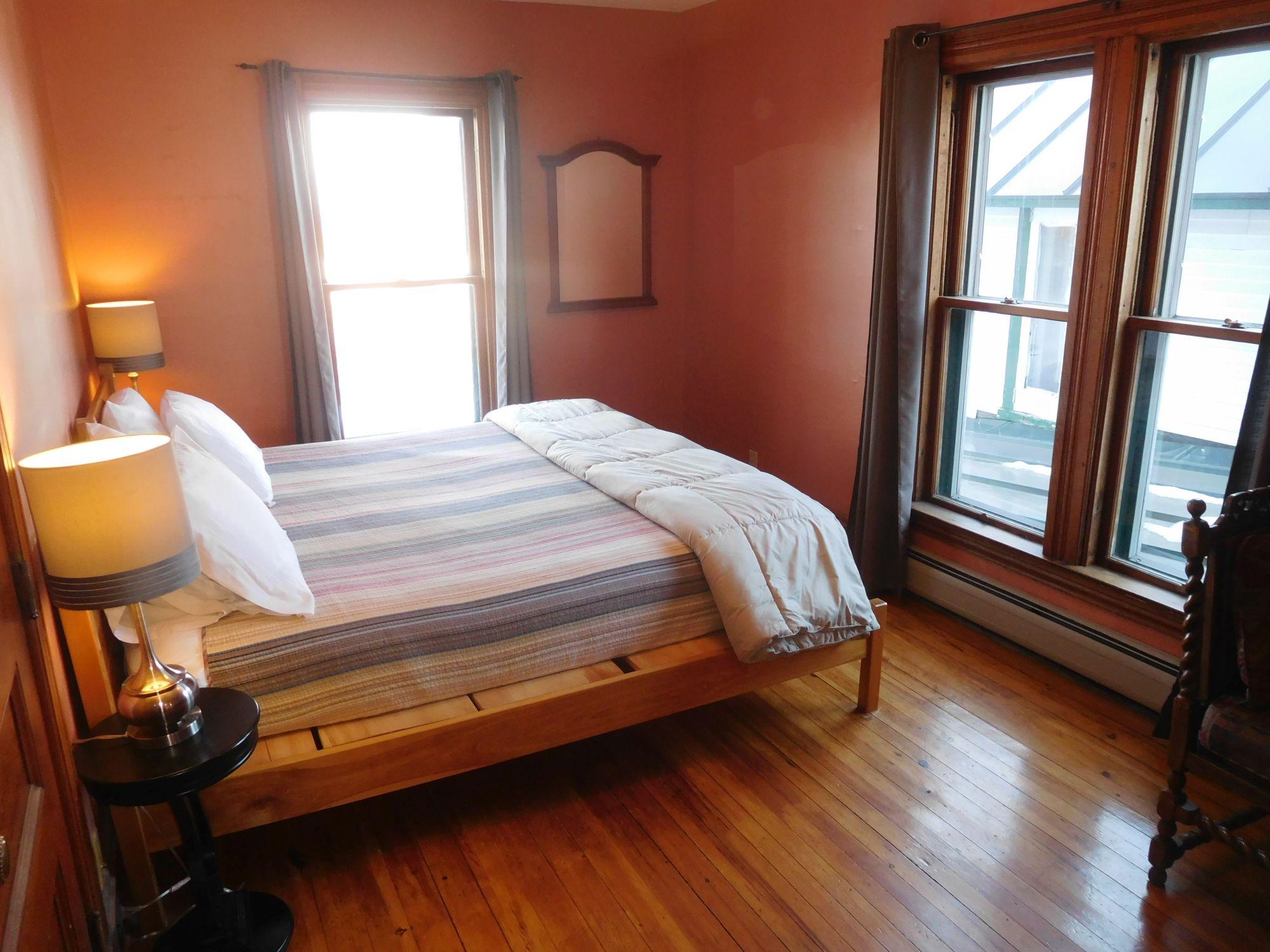 Master bedroom, handmade king bed, west windows facing the lake, sunset.