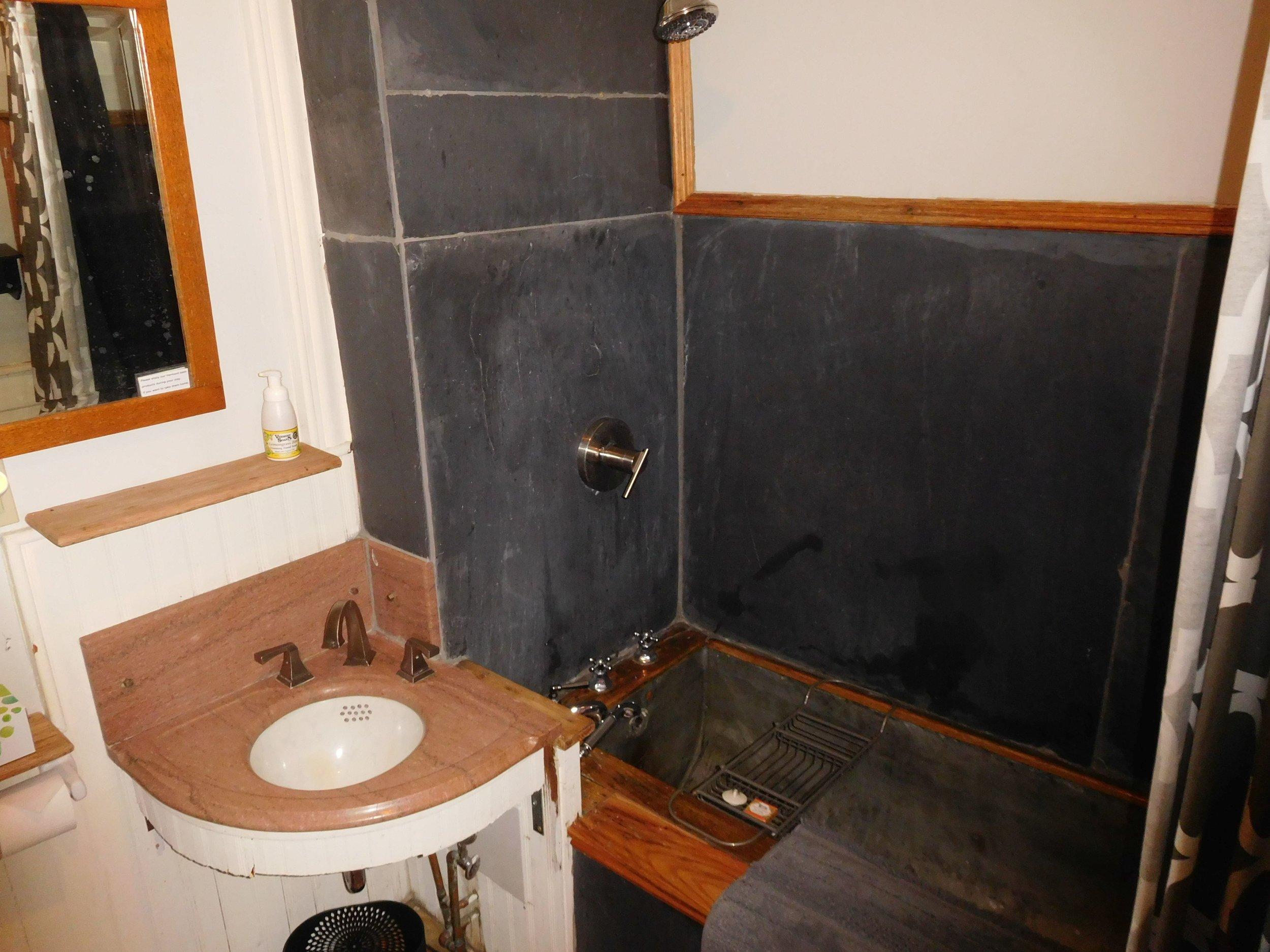 Original tin soaking tub, marble sink, re-purposed slate slab walls