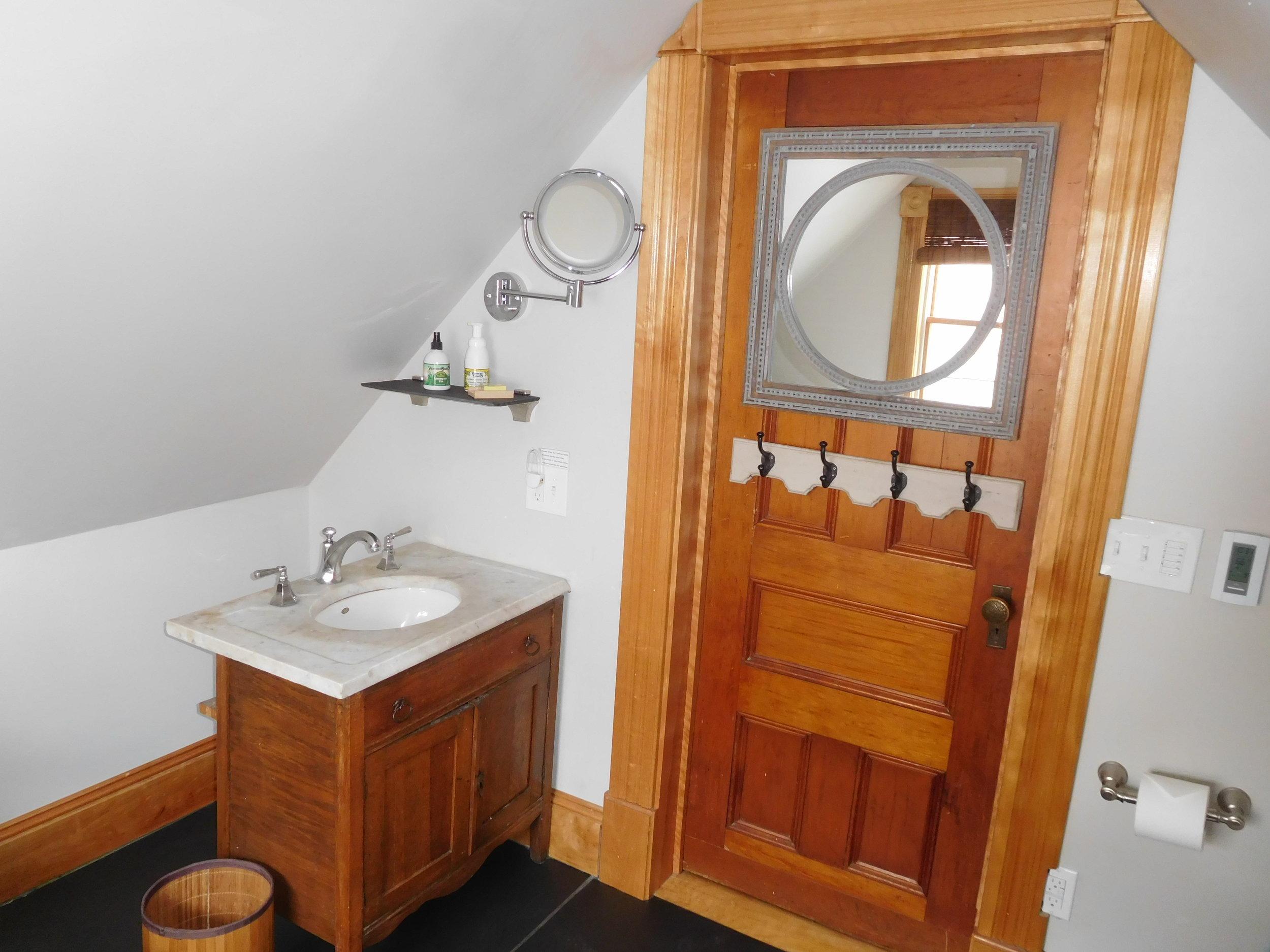 Carriage House upstairs bathroom, marble sink, slate floors, original doors.