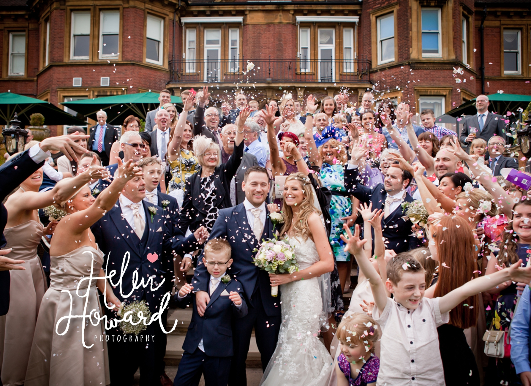 Bride and Groom surrounded by guests throwing confetti