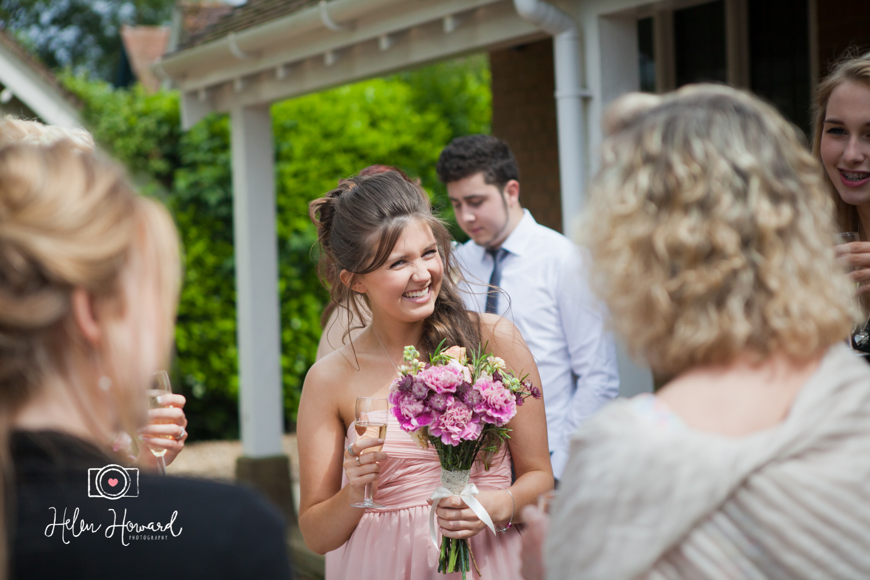 A bridesmaid smiling during drinks reception at Hastoe Hall in Tring
