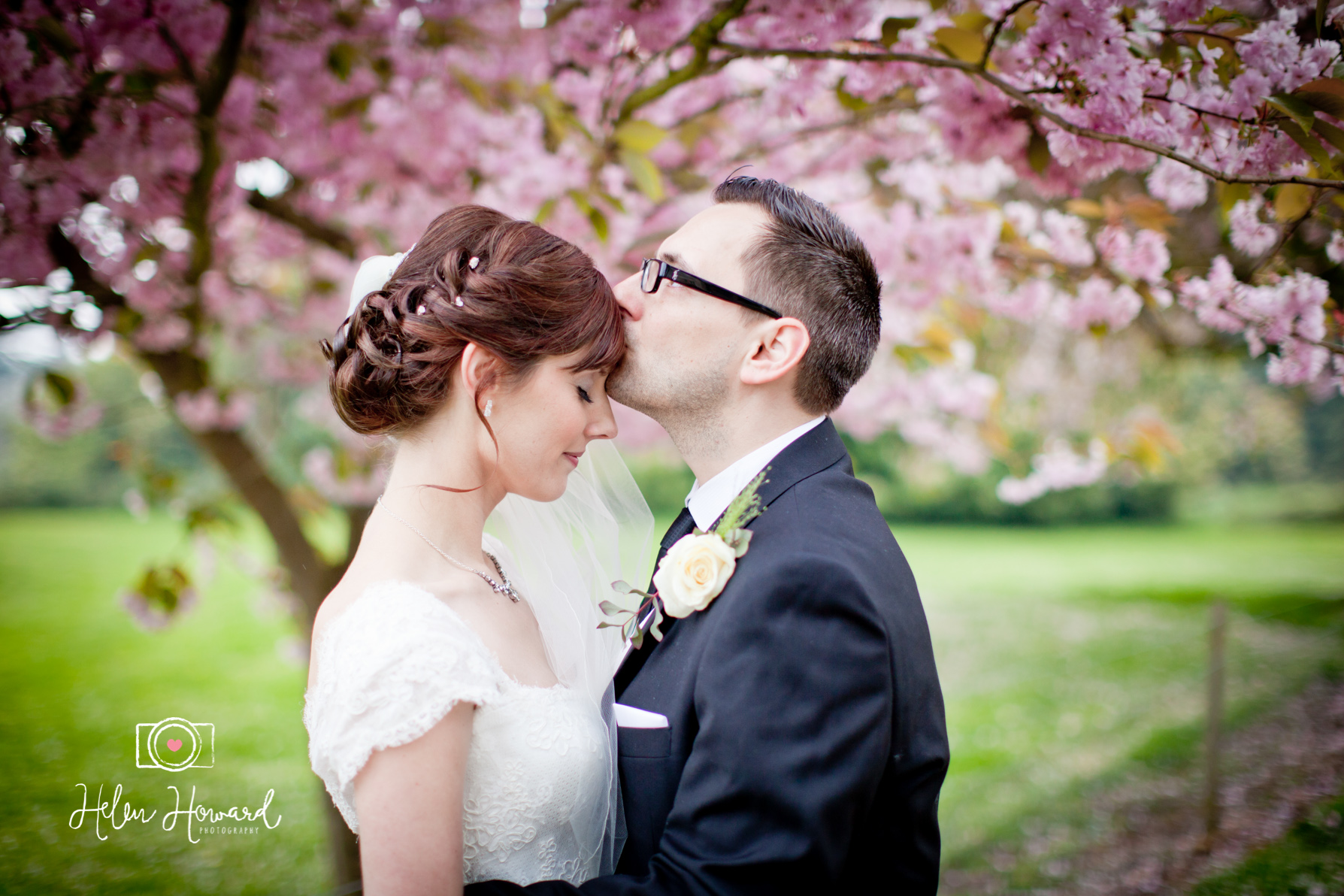 Bride and Groom kissing by the pink blossom tree at Down Hall Hotel