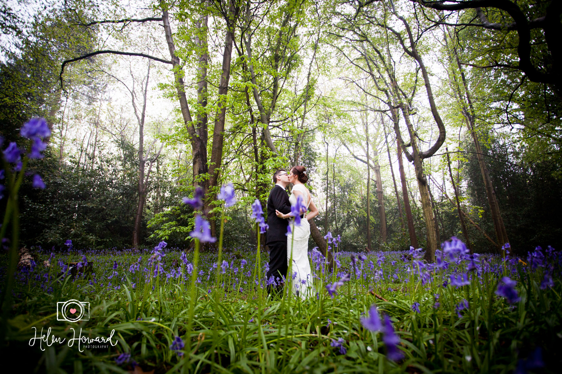 Kissing Bride and Groom in The bluebell woods at Down Hall Hotel