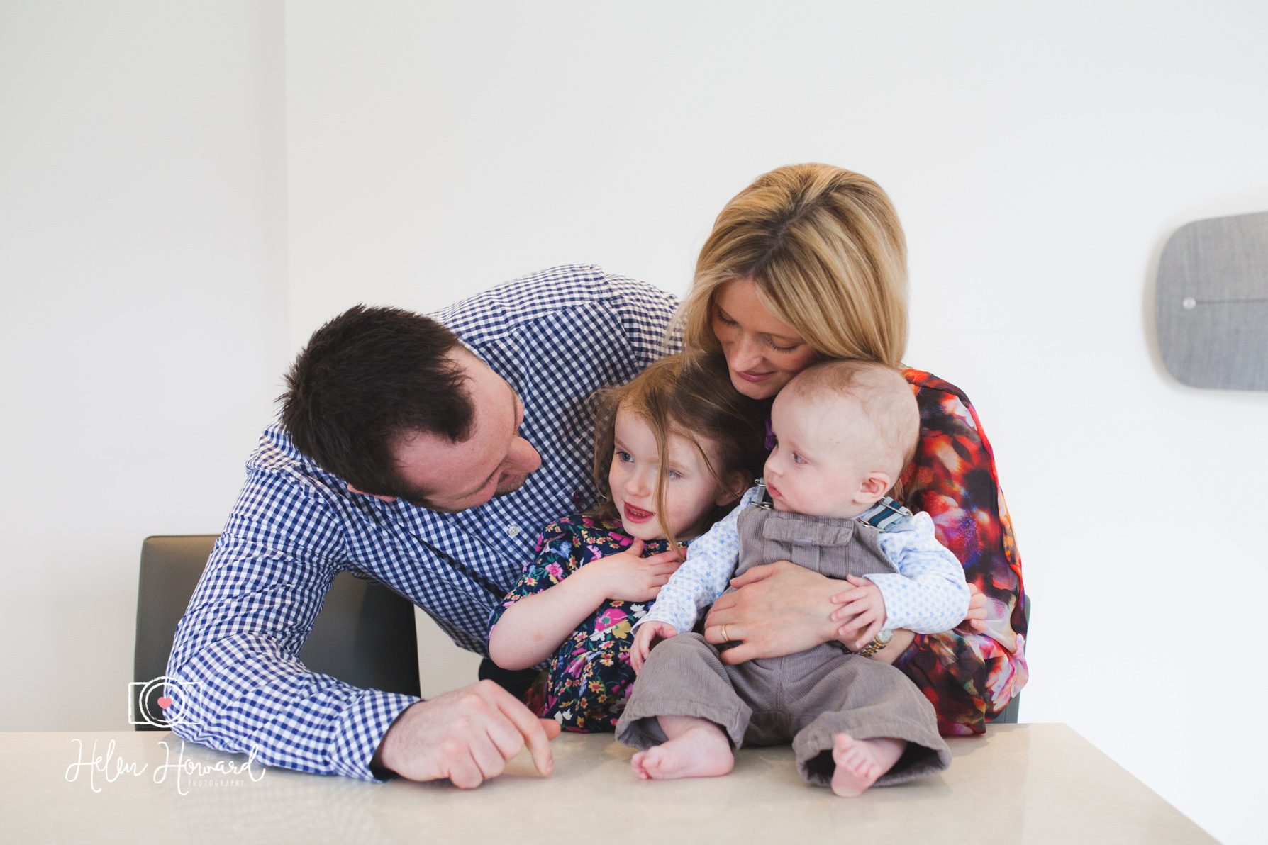 A family of four during a family portrait shoot at home