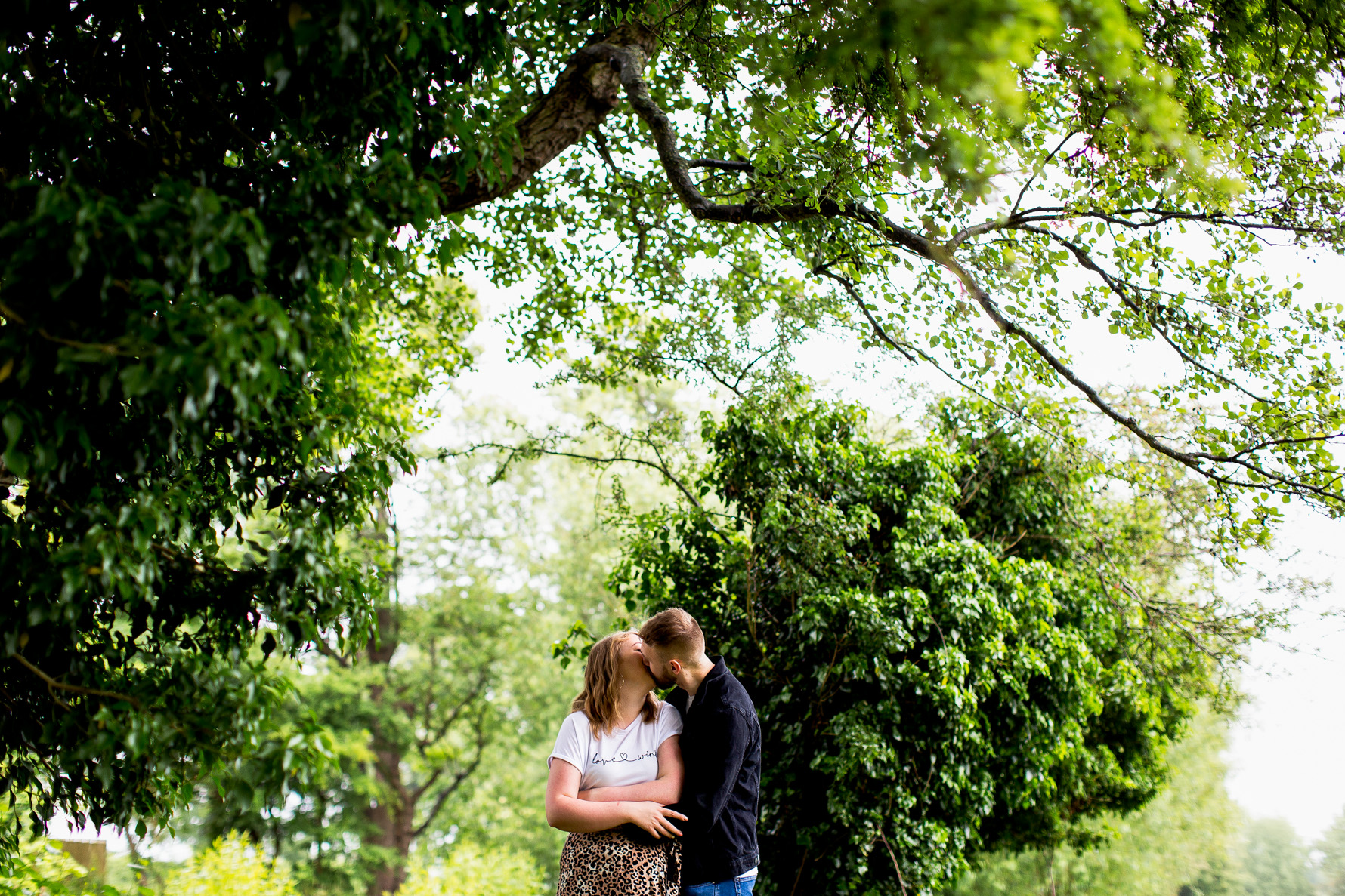 Engagement shoot couple kissing under the trees
