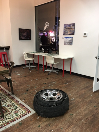 A tire burst through the west window, narrowly missing a coworker who had set up his computer along the adjacent bar.