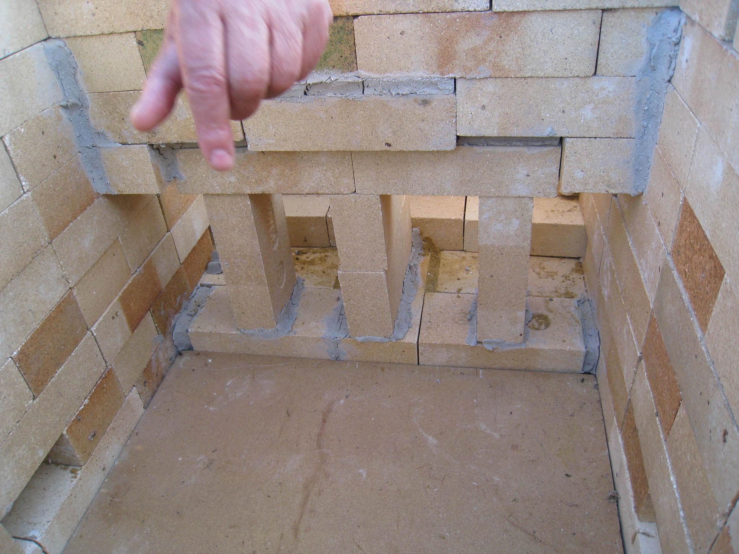 Esta es por supuesto otra opción: construirlo todo de ladrillo, tanto la pared interna de la chimenea como los soportes para el paso del fuego y el humo. En este horno, una compañera lo hizo así, cementando los ladrillos como se ve en esta imagen hecha desde el interior de la cámara de cocción.