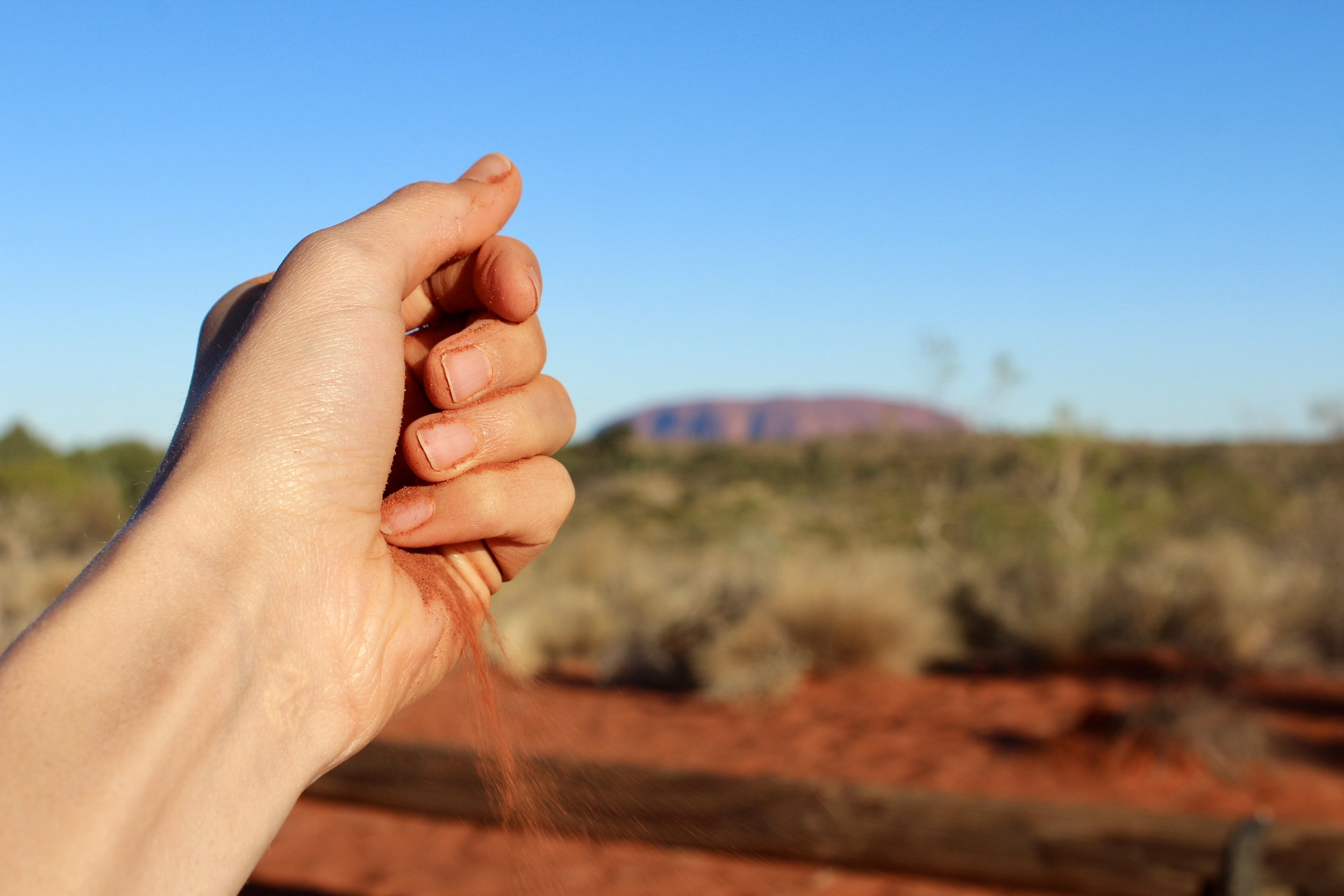 The dazzling red sand of the Outback with Uluru in the distance