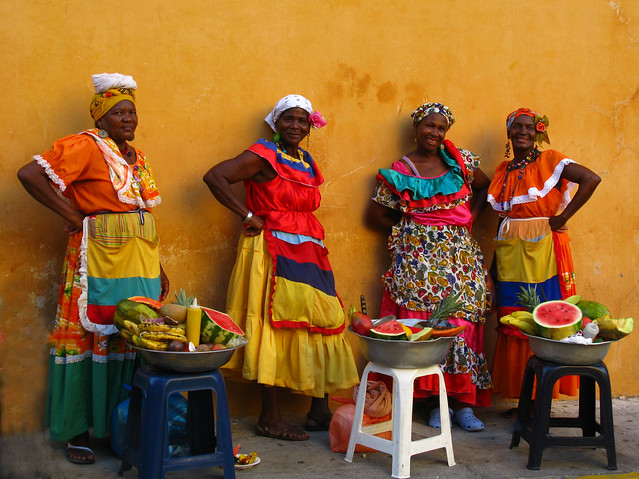 The iconic colorfully-clad, fruit-selling ladies you will see in Cartagena hail from Palenque.  Source