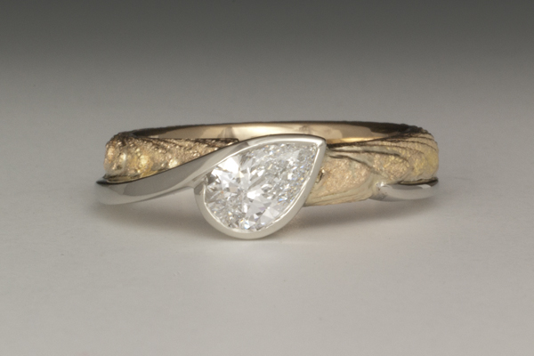 Pear shaped diamond solitaire in white gold accent bezel setting on a yellow gold cuttlefish cast band.