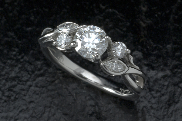 Prong set center diamond flanked with accent diamonds set in floral inspired forms.