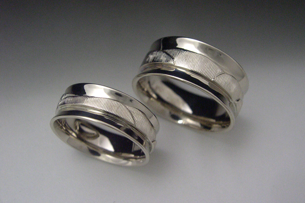Matching engraved white gold bands. The pattern depicts the skyline of a location of sentimental importantance to the couple.