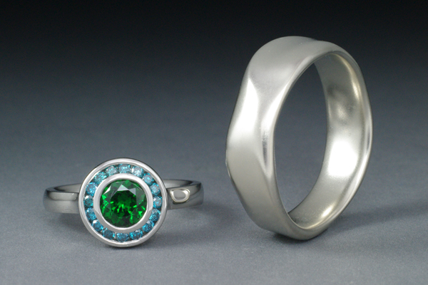 Engagement ring in white gold with a bezel set green tsavorite garnet surrounded with a channel set halo of blue diamonds.  Men's band in white gold in an organic sculptural form.