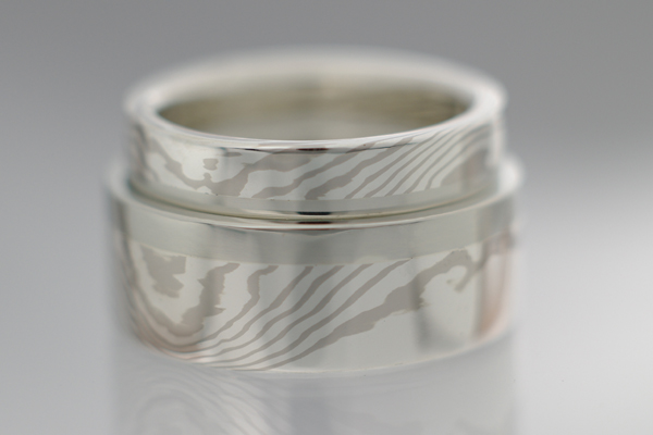 Couples Mokume bands created from the same billet with matched edges.