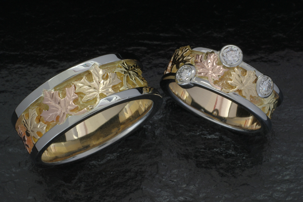 Redesigned wedding bands.  Custom design features a maple leaf motif in red, green and yellow gold with white gold edges and bezel set diamonds on the lady's band.