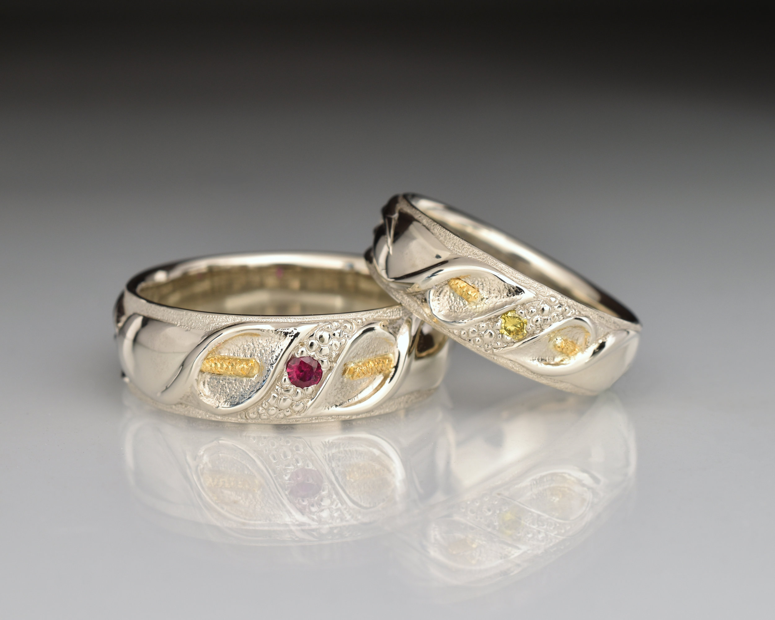 18k White Gold wedding bands, inspired by the Calla Lily. Gents band set with ruby and Ladies band set with yellow diamond.