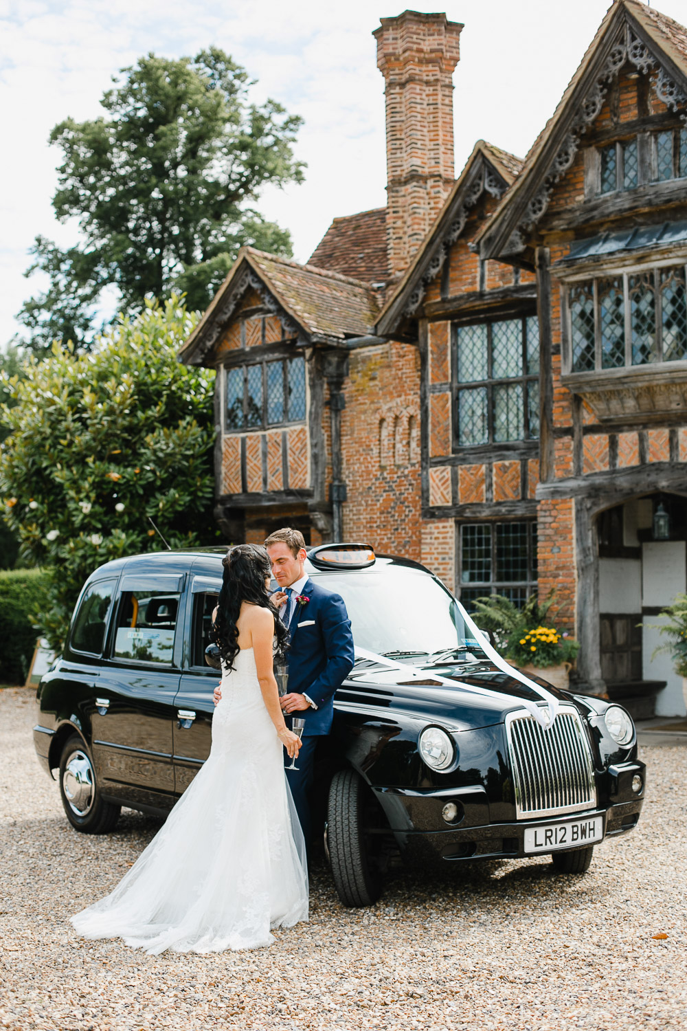 bride and groom with black cab at dorney court
