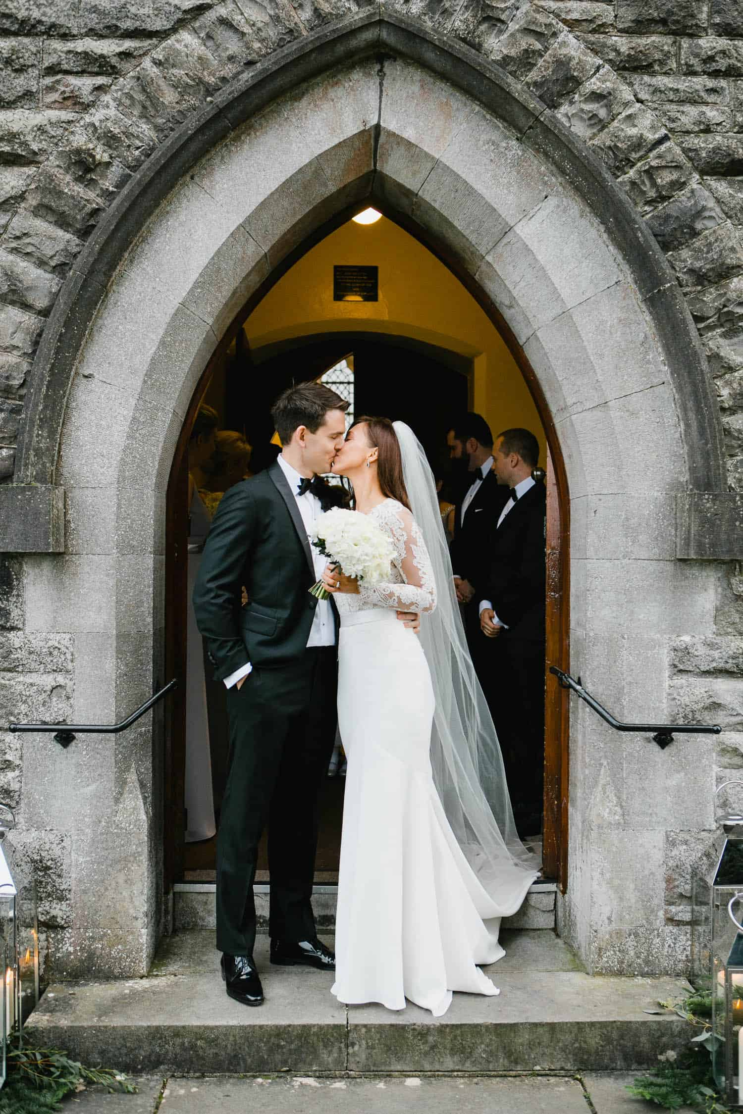 Bride and Groom Kiss Outside Rathfeigh Church Entrance