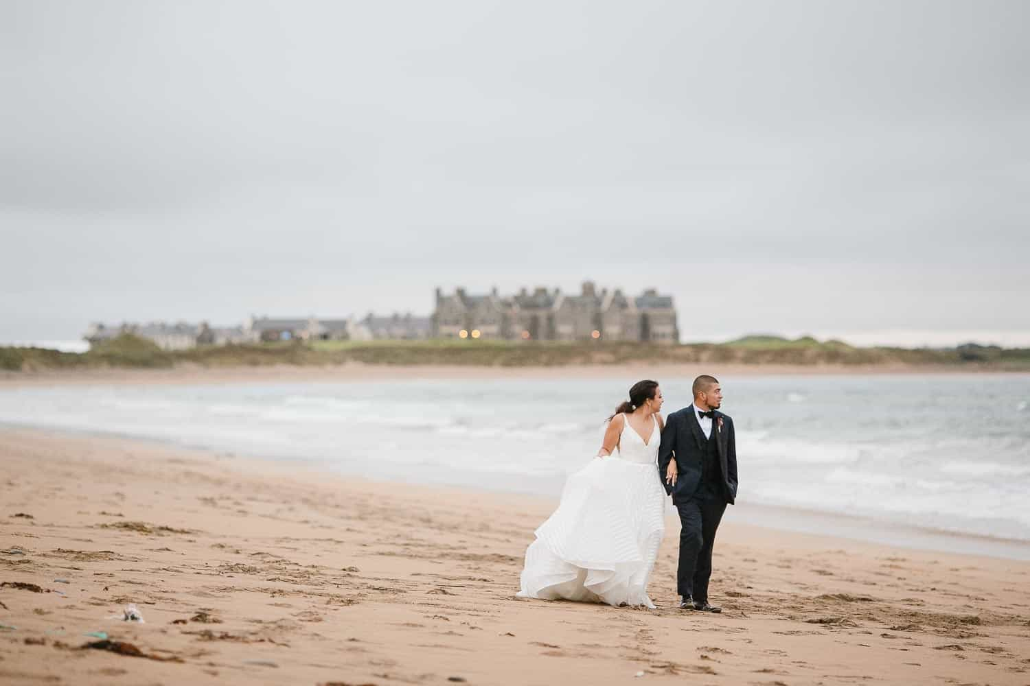 Bride and Groom Walking on the Beach Outside Trump Doonbeg Hotel